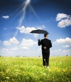 13264233-a-businessman-holding-an-umbrella-in-a-storm